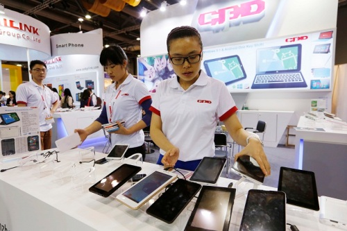 Staff members show the Chinese made tablets in a booth at the Global Sources Spring China Sourcing Fair in Hong Kong Saturday, April 12, 2014. As China's economy downshifts, manufacturers like Linan Meite Cable are bracing for the turning point that's in store for the world's second biggest economy.  (AP Photo/Kin Cheung)