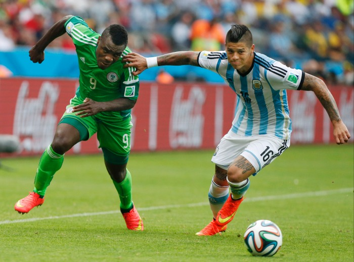 Argentina's Marcos Rojo, right, pushes off Nigeria's Emmanuel Emenike as they struggle for the ball during their group F World Cup soccer match at the Estadio Beira-Rio in Porto Alegre, Brazil, Wednesday, June 25, 2014. (AP Photo/Jon Super)