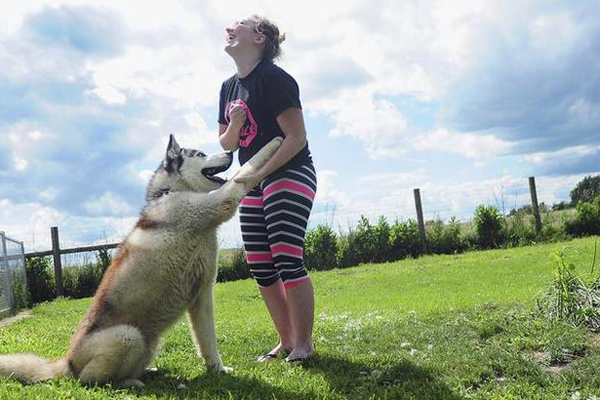 Woman playing with a husky outdoors