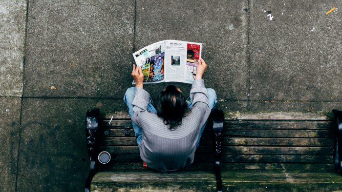 Man reading newspaper while sitting on a bench with cup of coffee