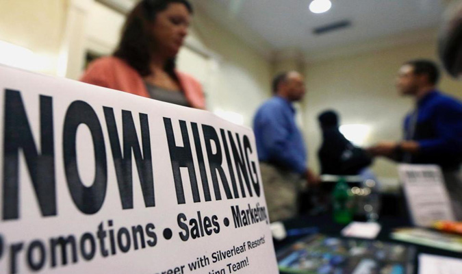 Sign on table reading: Now Hiring - Promotions, Sales, Marketing.