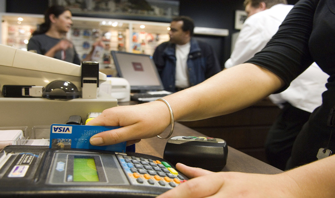 Cashier using a credit card machine at the register