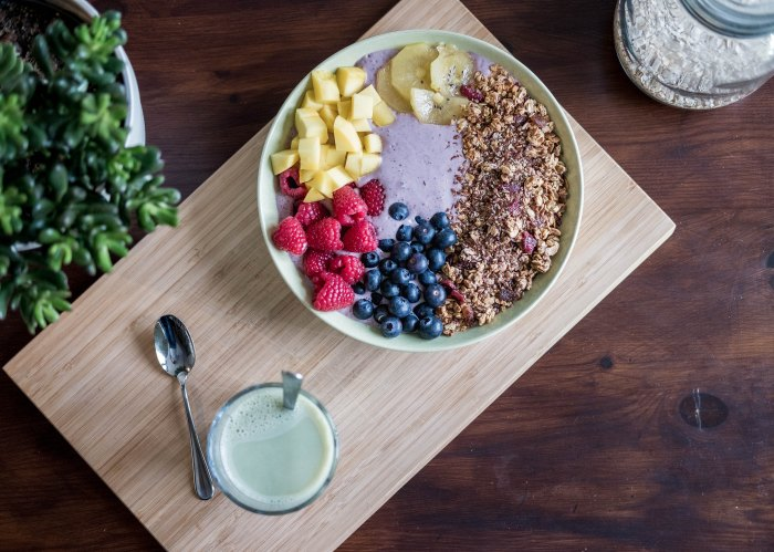 Photo of a bowl of superfoods, with fruit and oats and a green beverage next to the bowl