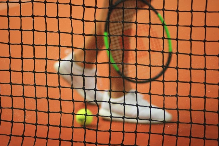 View of a tennis player's feet, racket and tennis ball through the net