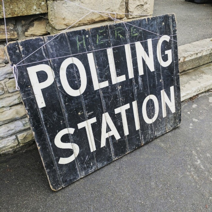 Black and white polling station sign leaning against a set of steps