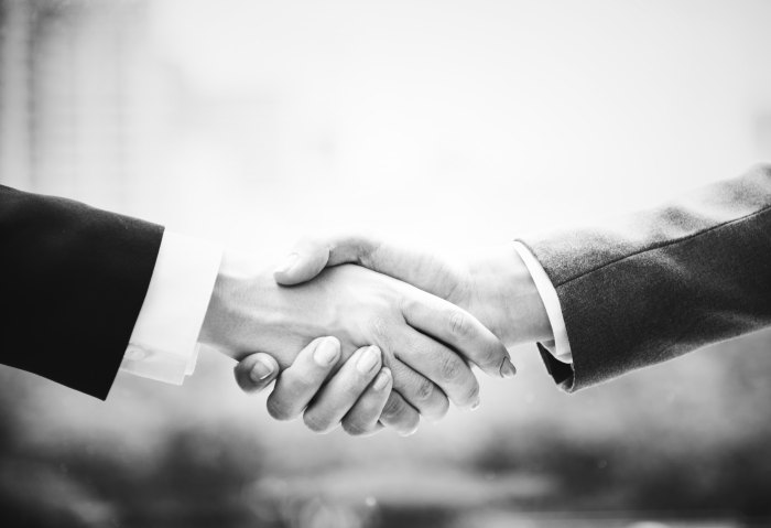 Black and white photo of two people shaking hands