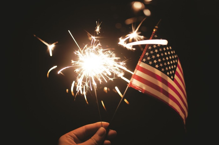 Hand holding a lit sparkler and American flag