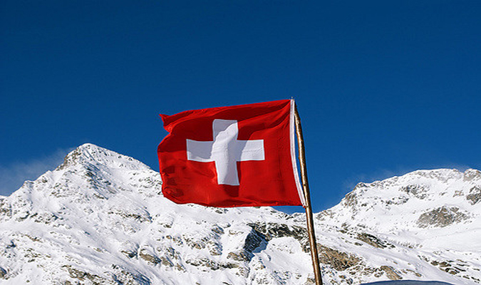 Swiss flag flying in front of snow-covered mountains