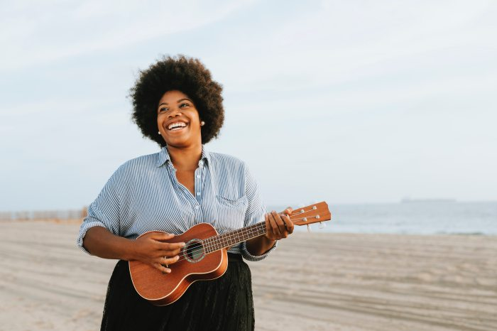 Pros and Cons of Posed and Unposed Photography: African American woman smiling and holding a ukulele on the beach.