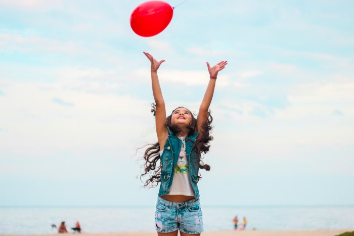Pros and Cons of Posed and Unposed Photography: Young girl at the beach jumping up to reach a red balloon.
