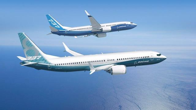 Two Boeing 737 planes flying next to each over over water.