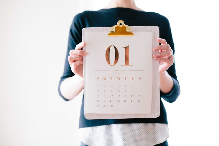 Woman holding up a clipboard with a monthly calendar for January attached