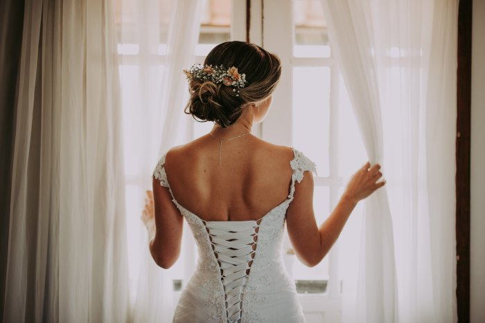 Woman in a bridal gown looking out a window