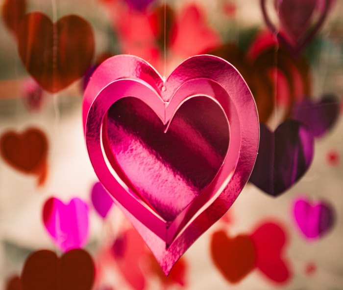 Cutout hearts in pink paper hanging from strings