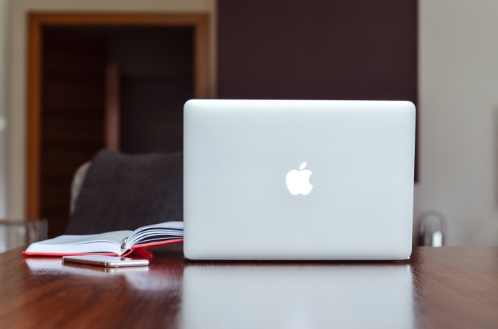 Apple computer, phone and book sitting on desk