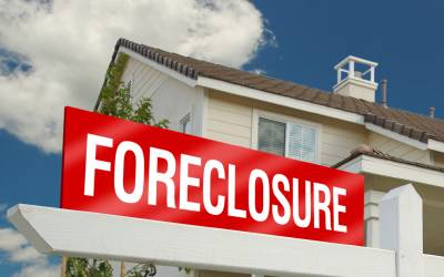Red foreclosure sign in front of a white two-story home