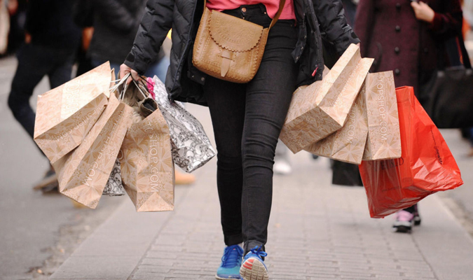 Person walking while carrying multiple shopping bags.