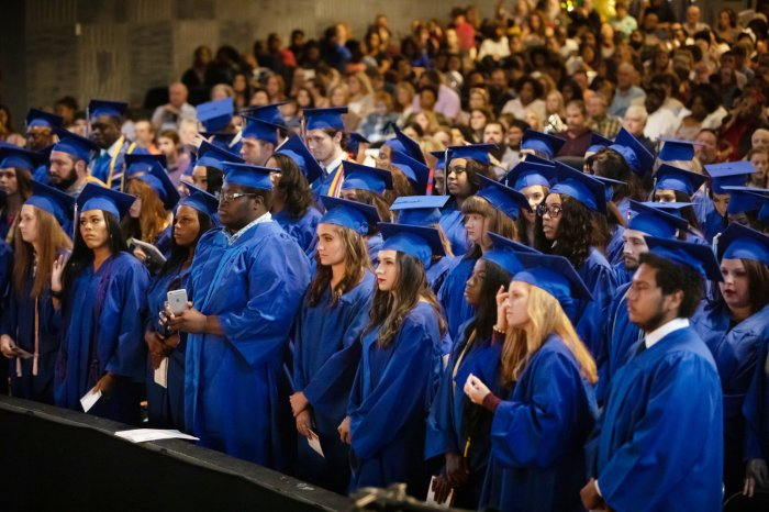 A group of college graduates in blue caps and gowns.
