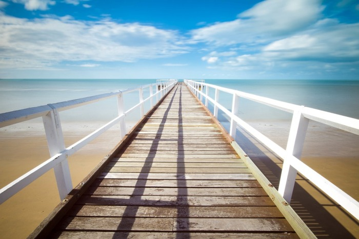 Wooden beach walkway leading out over the water.