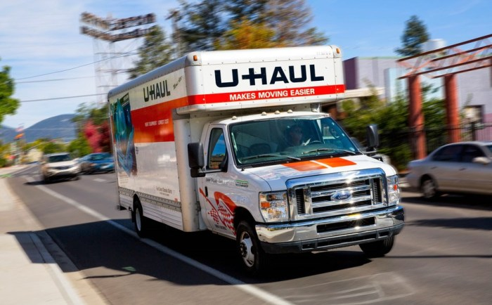 U-Haul moving truck driving down a busy street