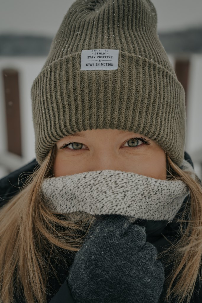 Close-up portrait of a woman wearing a beanie and scarf in the snow