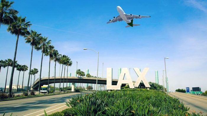 Airplane flying over LAX airport sign