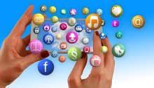 Hands holding smartphone while social media icons float around