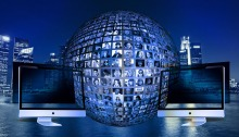 globe with faces on it, two computer monitors on either side, and a skyline in the background