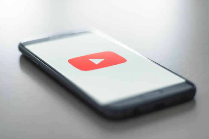 Smartphone on a desk with YouTube logo on the screen