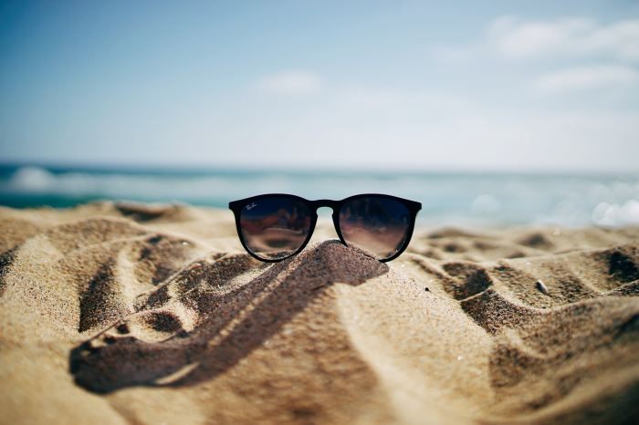 Pair of sunglasses laying atop the sand at the beach