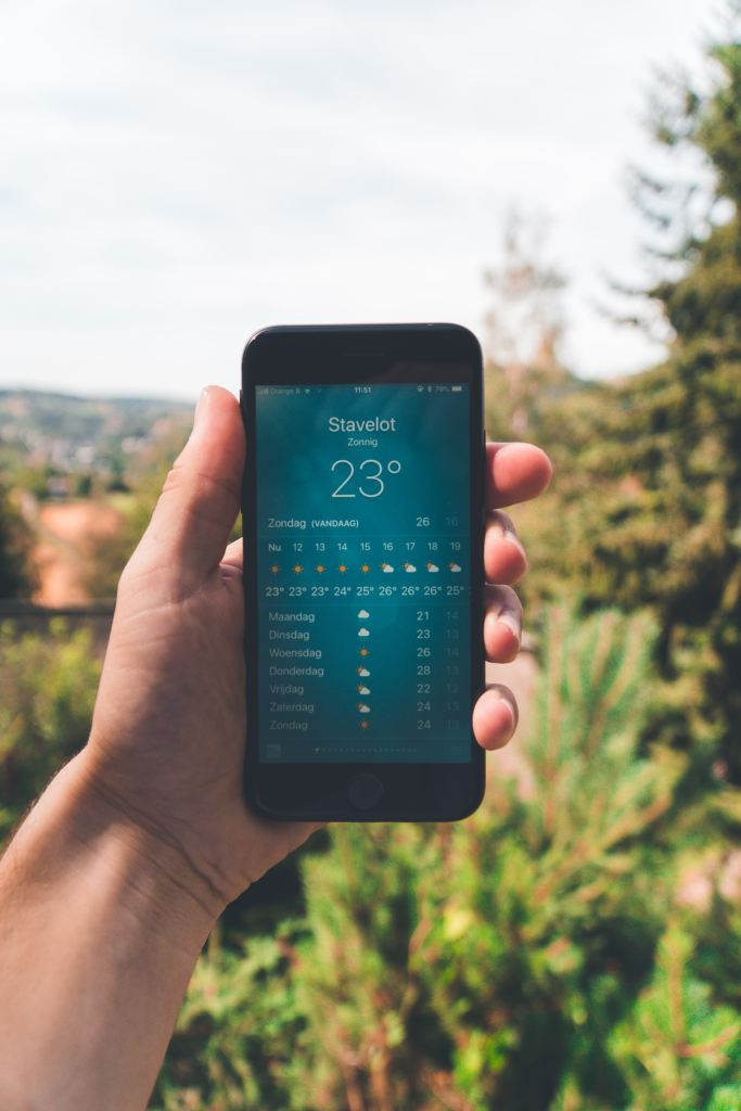 Hand holding a smartphone outdoors with a weather app on the screen