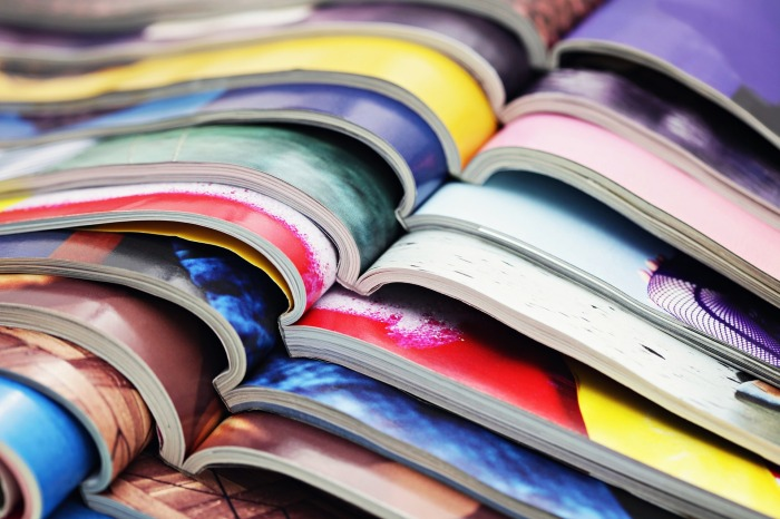 A stack of open magazines in different colors