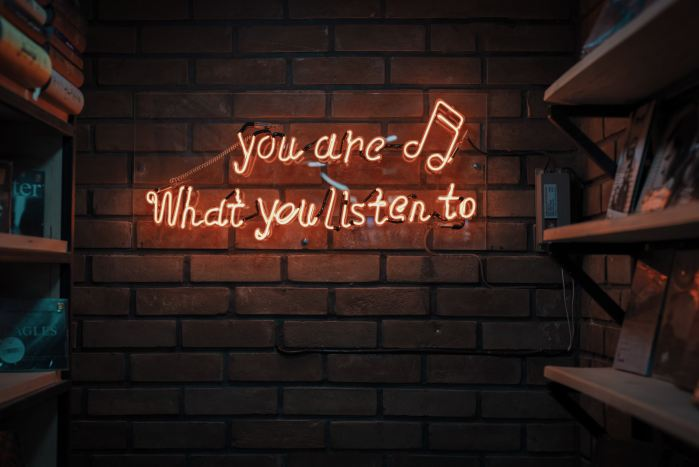 Neon sign on a brick wall reading: You are what you listen to