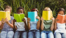 Row of young children holding up open books to read