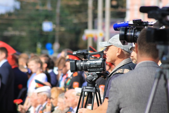 Broadcast reporters with cameras on location at an event