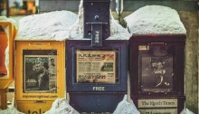 Several newspaper box stands on the street covered in snow