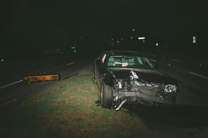 A wrecked car left in the road at night