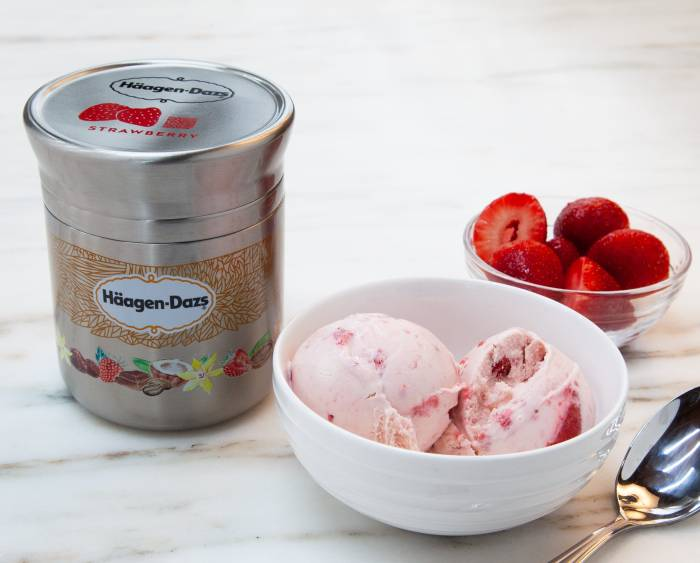 Nestle Haagen-Dazs strawberry ice cream container next to two bowls with scoops of ice cream and sliced strawberries