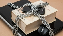 Media Insider - Feb 14 2020 - Image of a laptop, book, smartphone and computer mouse bound in a chain