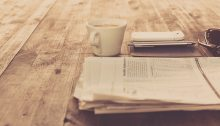 Media Insider - 2/7/20 - Cup of coffee on a desk next to a folded newspaper and smartphone