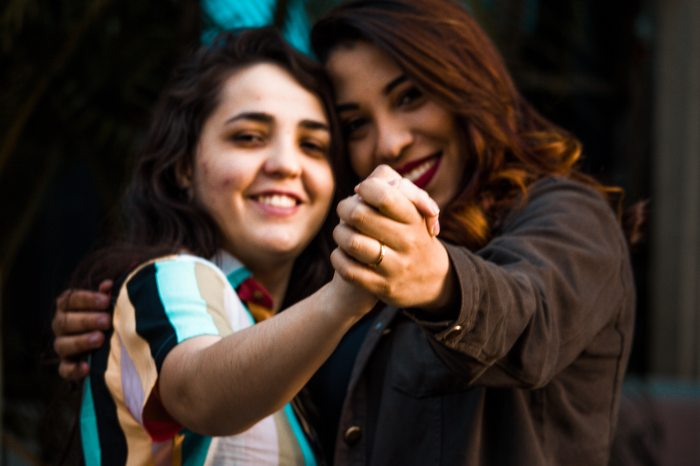 Couples Photography Tips - closeup of female couple holding hands and smiling