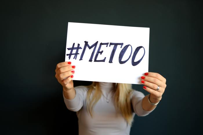AP Style Reminders - #MeToo - image of a woman holding up a white sign with #MeToo written on it