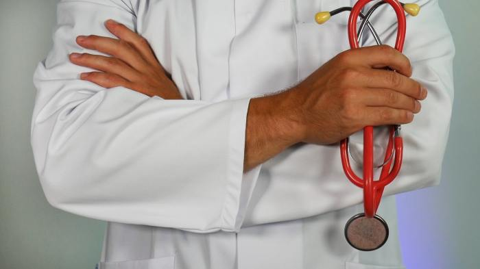 closeup of a doctor in a white coat holding stethoscope