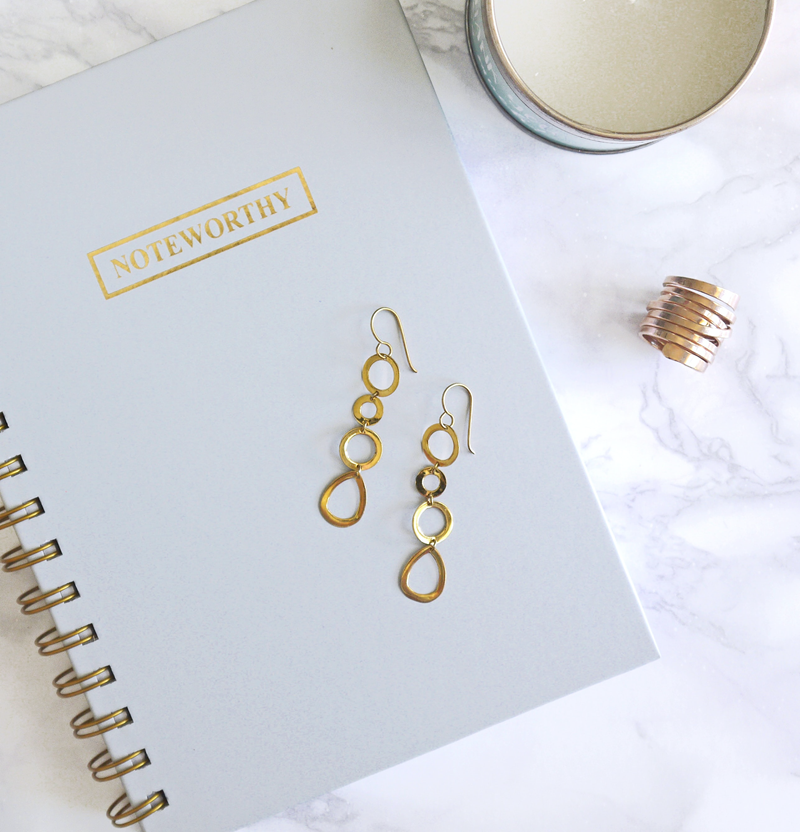 Gold earrings and a gold ring laying on top of and next to a notebook