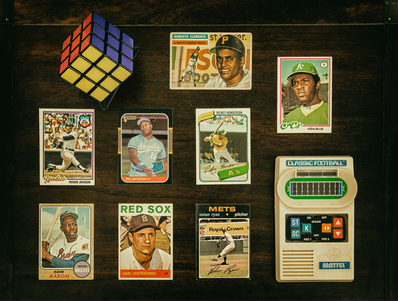 Photo of collectible items including baseball cards, Rubiks Cube and a handheld video game