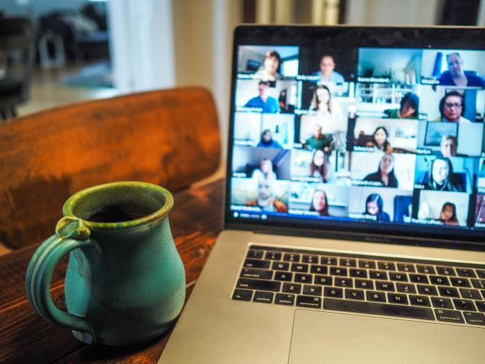 work from home setup with a cup of coffee and laptop showing a virtual meeting