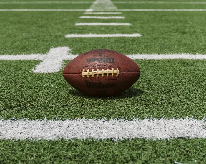Stock image of a football on the field, near a yard marker line
