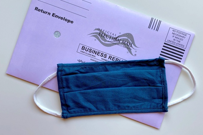 Picture of a mail-in voting envelope with a blue face mask laying on top of it