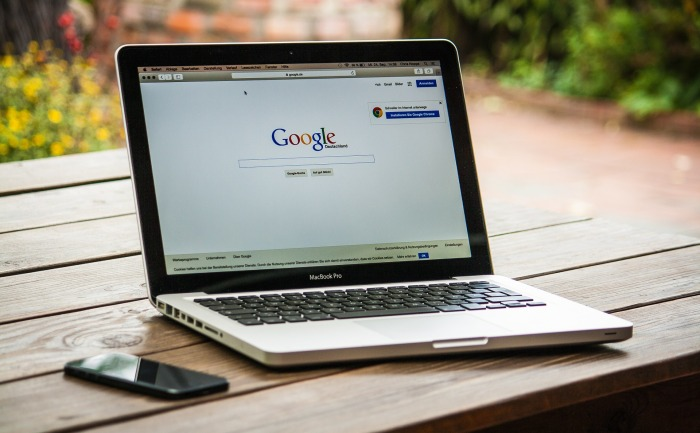Photo of an open laptop on an outside table, screen shows the Google homepage, a smartphone is next to the laptop