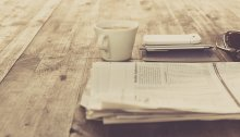 A folded newspaper on top of a table, next to a cup of coffee, smartphone, and pen